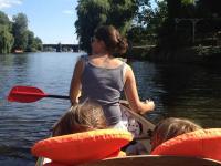 Eine Frau mit zwei Kindern paddelt durch einen Fluss.