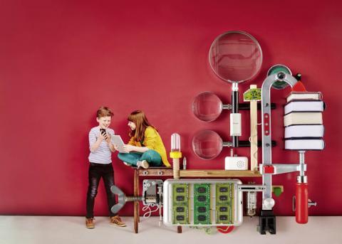 Zwei Kinder beraten vor einer riesigen Lupen-Maschine