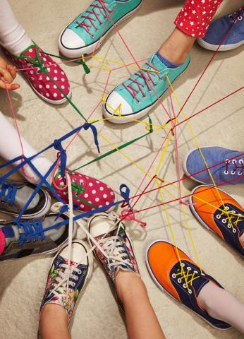 Bunte Kinderturnschuhe vernetzen sich über Schnürsenkel