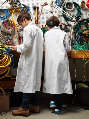 Zwei junge Erfinder in weißen Kitteln stehen im Kabellabor