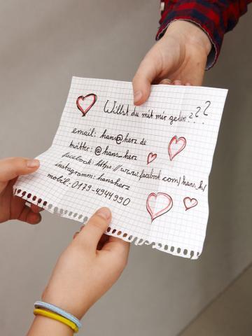 Kinderhände übergeben einen Zettel mit Frage und persönlichen Daten