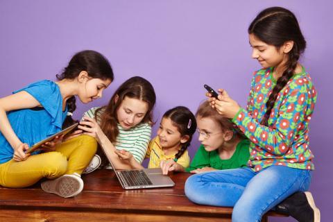 Fünf Mädchen schauen auf ein Smartphone, ein Tablet und ein Laptop