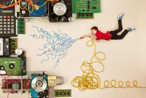 Ein Junge löscht mit einem Kabelschlauch verschiedene Computer und Geräte