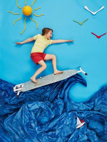 Ein kind surft fröhlich auf Papierwellen und Bügelbrett